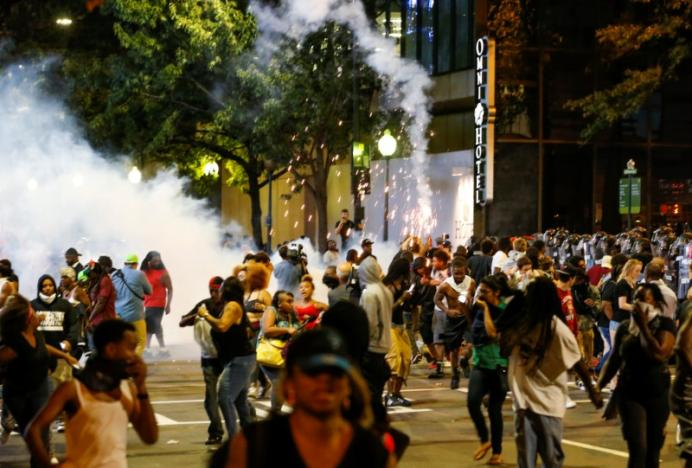 People run from flash-bang grenades in uptown Charlotte during a protest of the police shooting of Keith Scott. REUTERS/Jason Miczek